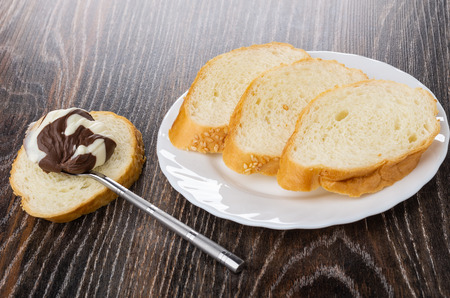 Spoon with dairy chocolate-nut paste on piece of bread, pieces of bread in white plate on dark wooden table 免版税图像