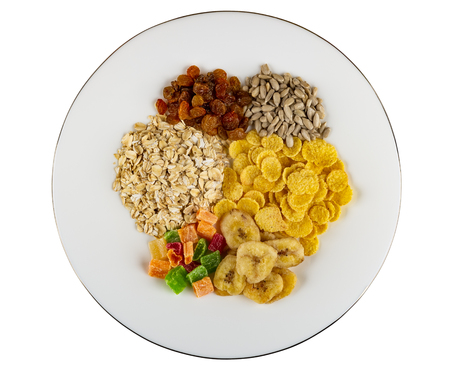 Heap of different ingredients for muesli (dried fruits, corn flakes, oatmeal, sunflower seeds, banana chips) in glass dish isolated on white background. Top view Reklamní fotografie