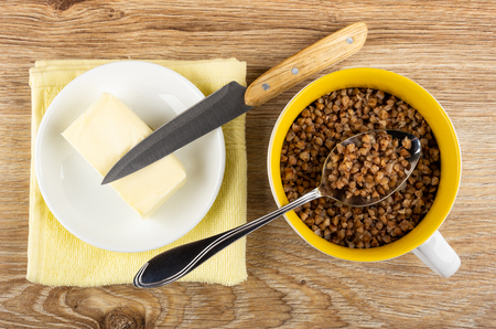 Butter in saucer on napkin, kitchen knife, boiled buckwheat, spoon in glass yellow bowl on wooden table. Top view Stock Photo