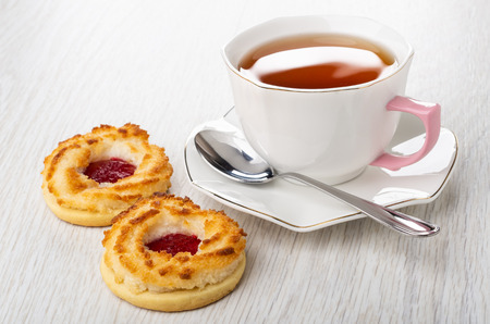 Cup of tea, spoon on saucer, shortbread cookies with jam on light wooden table