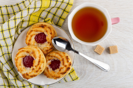 Shortbread cookies with jam in white plate, teaspoon on checkered napkin, cup of tea, sugar cubes on light wooden table. Top view 免版税图像
