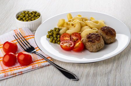Tomato cherries, fork on napkin,bowl with green peas, white plate with cooked pasta cavatappi, fried patties, green peas, tomato on light wooden table