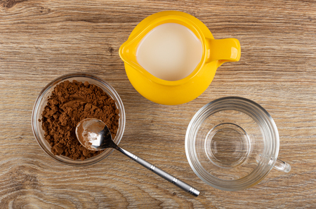 Cacao powder in bowl, teaspoon, jug of milk, empty transparent cup on wooden table. Top view