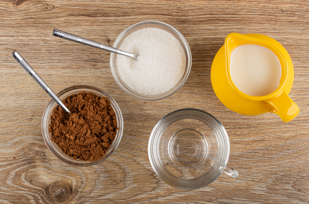 Cacao powder, teaspoon in bowl, teaspoon in bowl with sugar, pitcher with milk, empty transparent cup on wooden table. Top view