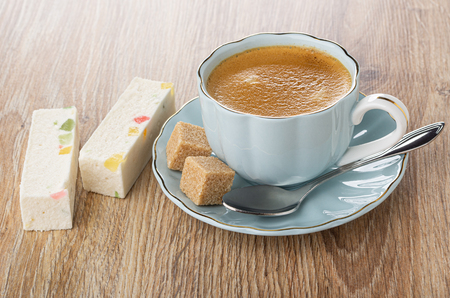 Two pieces of nougat with marmalade, coffee in cup, sugar cubes, spoon on saucer on wooden table 写真素材