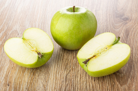 Halves of green apple, whole apple on wooden table