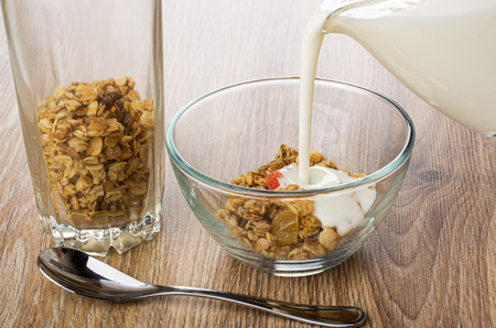 Tall transparent glass with fruit muesli, yogurt poured on granola in transparent bowl, teaspoon on wooden table