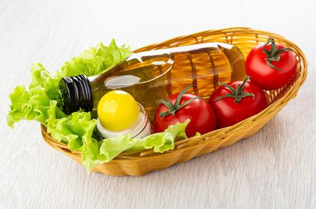 Bottle of vegetable oil, salt shaker, leaves of lettuce, red fresh tomatoes in wicker basket on wooden table