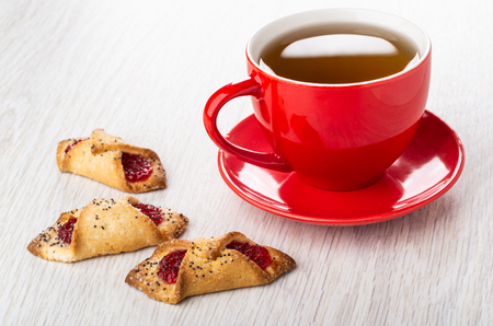 Three shortbread envelope cookies with jam, red cup with tea on saucer on wooden table