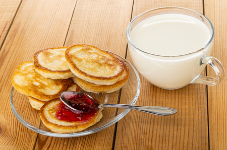Fried homemade pancakes, spoon with raspberry jam on pancake in transparent saucer, cup of milk on wooden table