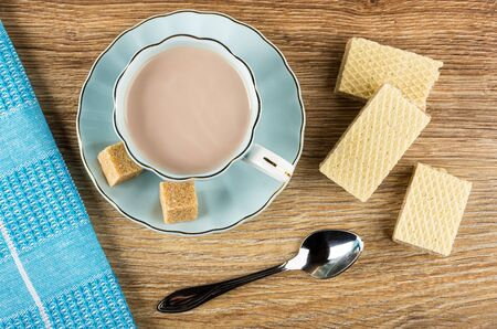 Napkin, cocoa with milk in blue cup, sugar cubes on saucer, pieces of wafers, teaspoon on wooden table. Top view 免版税图像