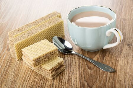 Cocoa with milk in blue cup, pieces of wafers, teaspoon on wooden table