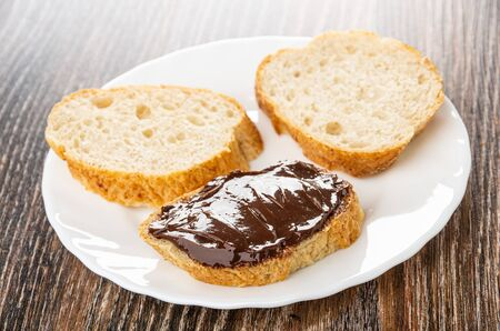 Slices of bread, sandwich with chocolate melted cheese in white plate on wooden table