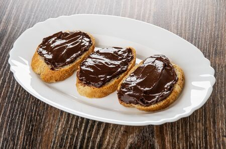 Sandwiches with chocolate melted cheese in white dish on wooden table