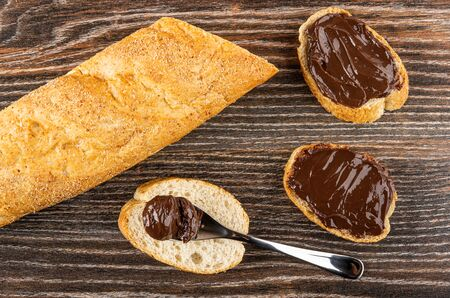Loaf of bread, chocolate melted cheese in spoon on slice of bread, sandwiches with melted cheese on wooden table. Top view