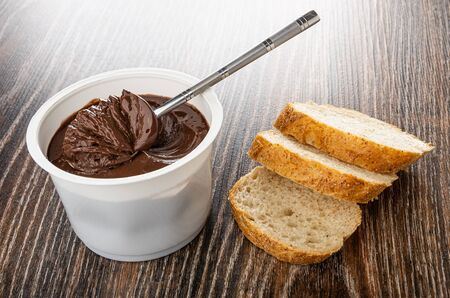 Teaspoon with chocolate melted cheese in white plastic jar, slices of bread on wooden table