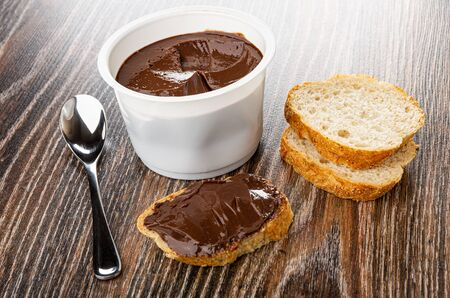 Teaspoon, white jar with chocolate melted cheese, sandwich with melted cheese, slices of bread on wooden table Stok Fotoğraf