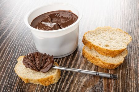 Teaspoon with chocolate melted cheese, melted cheese in white plastic jar, slices of bread on wooden table Stok Fotoğraf