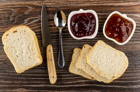 Bowls with apricot jam, currant jam, teaspoon, kitchen knife, slices of wheaten bread on dark wooden table. Top view
