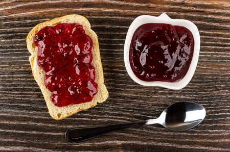 Sandwich with currant jam, bowl with jam, teaspoon on dark wooden table. Top view