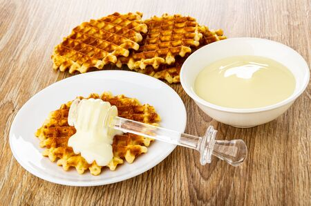 Poured condensed milk, transparent dipper on round wafer in white saucer, wafers, bowl with condensed milk on wooden table