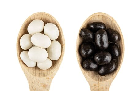 Black and white dragee in bamboo spoons (peanut in sugar and cocoa glaze) isolated on white background. Top view Imagens