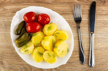 White dish with pieces of baked potato, marinated tomatoes, gherkins, dill, fork and knife on wooden table. Top view Reklamní fotografie - 127579837