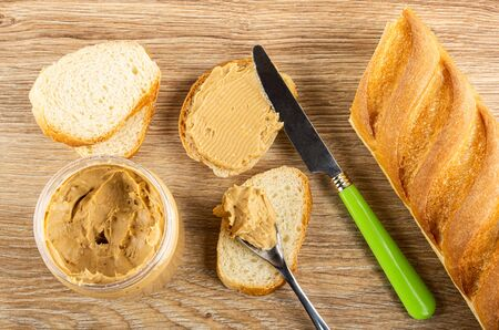 Slices of wheat bread, knife on sandwich, plastic jar with peanut butter, teaspoon with butter, loaf of bread on wooden table. Top view