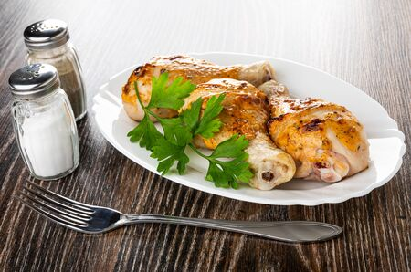 Salt and pepper shakers, grilled chicken legs and leaves of parsley in white dish, fork on dark wooden table Imagens