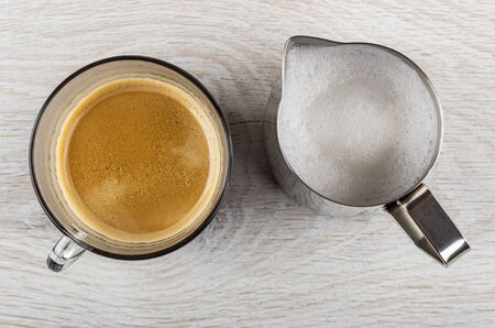 Coffee espresso in transparent glass cup, metallic pitcher with whipped milk on light wooden table. Top view