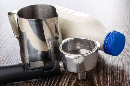 Bright metallic pitcher, lying transparent plastic bottle with milk, portafilter on dark wooden table