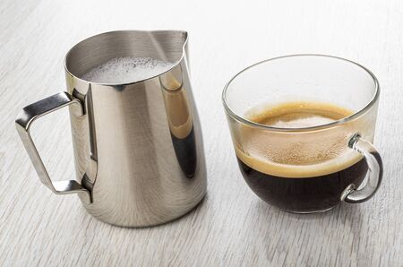 Bright metallic pitcher with whipped milk, coffee espresso in transparent glass cup on light wooden table
