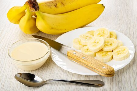 Bunch of bananas, slices of banana, kitchen knife in white plate, transparent glass bowl with condensed milk, teaspoon on wooden table