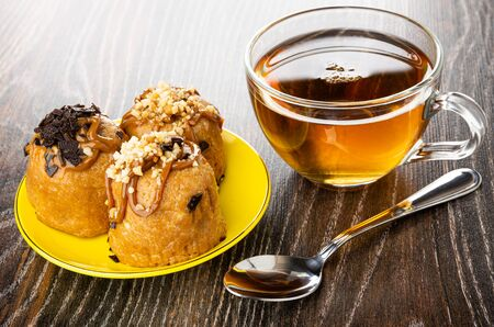 Three cakes with chocolate and peanuts in yellow saucer, transparent cup with tea, teaspoon on dark wooden table Imagens - 128902010