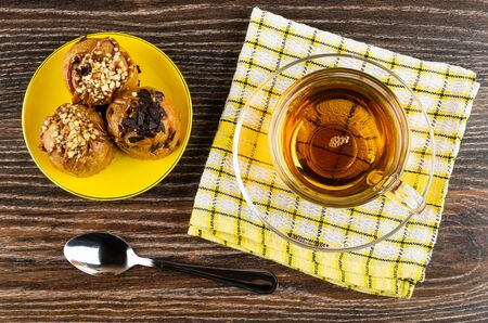 Cakes with chocolate and peanuts in yellow saucer, transparent cup with tea on saucer on checkered napkin, teaspoon on dark wooden table. Top view