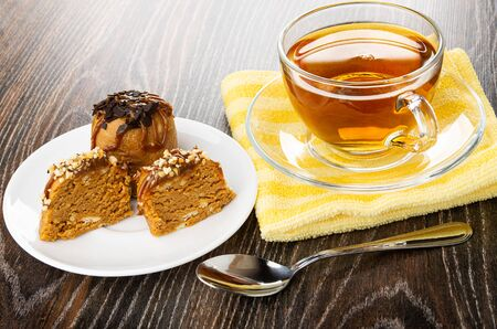 Cakes with chocolate, halves of cake with peanuts in white saucer, cup of tea and saucer on yellow napkin, teaspoon on dark wooden table Imagens