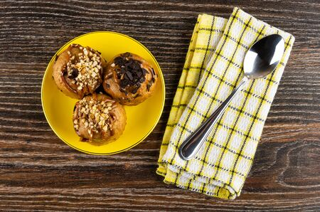 Cakes with chocolate and peanuts in yellow saucer, teaspoon on checkered napkin on dark wooden table. Top view Imagens - 128902022
