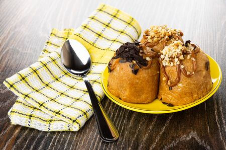 Teaspoon on checkered napkin, cakes with chocolate and peanuts in yellow saucer on dark wooden table