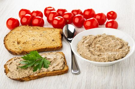 Tomato cherry, slices of bread, teaspoon, white bowl with liver pate, sandwich with pate and parsley on wooden table