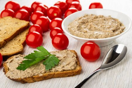 Slices of bread, tomatoes cherry, white bowl with liver pate, sandwich with pate and leave of parsley, teaspoon on wooden table