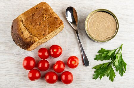 Loaf of bread, teaspoon, metallic jar with liver pate, red tomato cherry, leaves of parsley on wooden table. Top view
