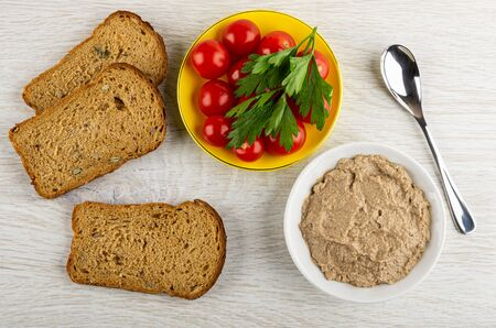 Slices of bread, red tomato cherry and parsley in saucer, white bowl with liver pate, teaspoon on wooden table. Top view