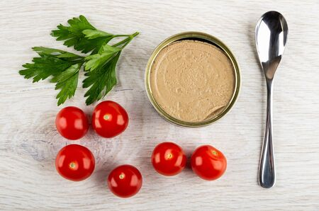 Leaves of parsley, metallic jar with liver pate, red tomato cherry, teaspoon on wooden table. Top view Banco de Imagens