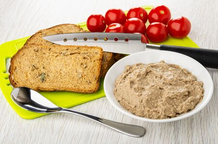 Pieces of bread, kitchen knife, tomato cherry on cutting board, teaspoon, white bowl with liver pate on wooden table 写真素材