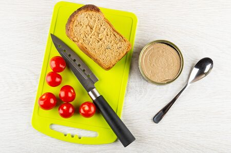 Loaf of bread, kitchen knife, tomato cherry on cutting board, metallic jar with liver pate, teaspoon on wooden table. Top view Banco de Imagens