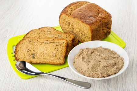 Pieces of bread on cutting board, teaspoon, white bowl with liver pate on wooden table 写真素材