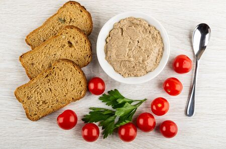 Slices of bread, white bowl with liver pate, red tomato cherry, leaves of parsley, teaspoon on wooden table. Top view 写真素材