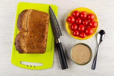 Loaf of bread on cutting board, kitchen knife, metallic jar with liver pate, tomato cherry in yellow saucer, teaspoon on wooden table. Top view