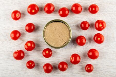 Metallic jar with liver pate and red tomato cherry on wooden table. Top view