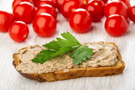 Many tomatoes cherry, sandwich with liver pate and leave of parsley on wooden table